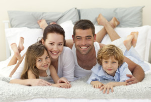 Happy family lying in bed together and smiling at the camera