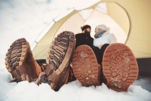 close up sole winter shoes. young couple sitting in tent in the snow and celebrating during winter vacation, summertime and holidays concepts.