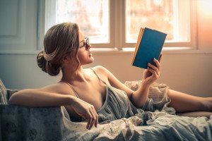 Sensual woman reading in bed