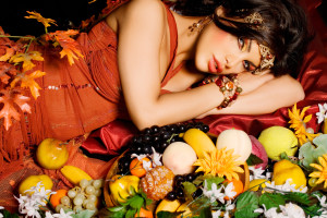 Woman laying down surrounded by fruit and flowers.