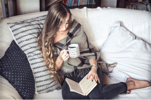 the girl with long hair dressed comfortably reading a book and drinking coffee on the couch in the background of the library the concept of reading and leisure time weekends