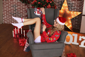fashion interior holiday Christmas photo of beautiful woman with blond hair in cozy home clothes and Santa hat celebrating New Year holidays
