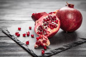 Red juice pomegranate on dark background