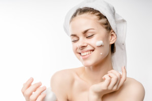 A woman in a towel on the head happy cleanses the skin with foam on a white background isolated. Skincare cleansing concept,copyspace