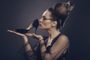 Fashion addicted sensual woman with loop of hair gently holding and kissing her new high heel shoe over dark background. Fashion and shopping addiction concept.