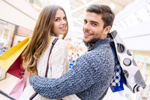 Happy young couple shopping and holding bags.Image taken inside a shopping mall.