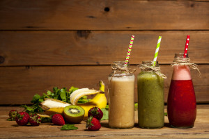 Assortment of fruit and vegetable smoothies in glass bottles with straws on wooden background.