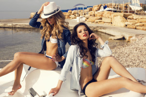 fashion photo of two beautiful sexy models in bikini relaxing on summer beach