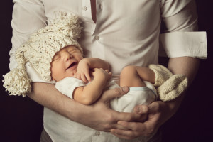 newborn baby boy smiling in woolen hat sleeping on father hand small kid happy laughing