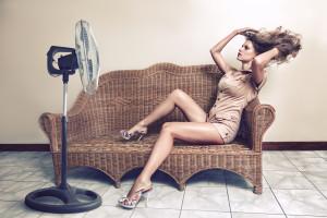 Young woman enjoying breeze with electric fan