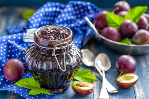 Plum jam and fresh fruits with leaves