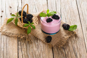 Bramble smoothie with berries on a rustic wooden table