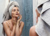 Beautiful woman with a towel on her head looking in the mirror and applying make up