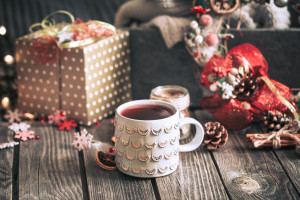 Homemade mulled wine on a wooden background with Christmas decor and a sweater, the concept of hot seasonal drinks