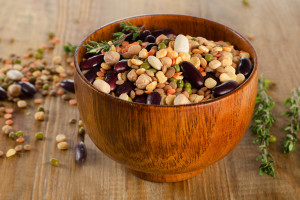 Multicolored mixed beans and lentils on a rustic wooden table