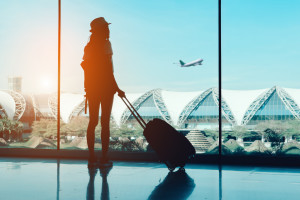 Silhouette woman travel with luggage looking without window at airport terminal international or girl teenager traveling in vacation summer relaxation holding suitcase and backpack