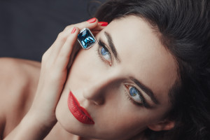 Chic style. Close-up portrait of sensuality beautiful woman model face with fashion make-up, sexy evening red lips makeup and bright red manicure, red lipstick, blue eyes, blue sapphire jewelry ring
