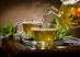 horizontal photo of the glass teapot flow green tea in cup on brown background tea ceremony