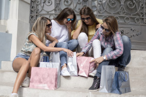 Shopping with a smile.Shopping fun. Beautiful girls talking about shopping, girls talk. Shopping and perfect mood.