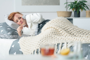 Ill woman lying in bed looking at thermometer suffering from seasonal flu and infectious disease