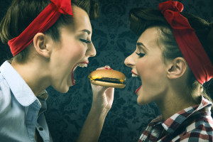Vintage girlfriends in old style dress eat hamburgers