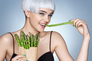 Young girl with green asparagus. Photo of smiling blonde girl on blue background. Detox concept