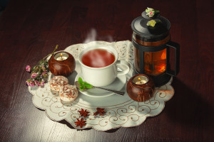 Cup of tea and teapot on dark background