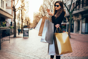 Shopper woman shopping with a smartphone in a city street. Caucasian female standing along the road holding shopping bags and using mobile phone.