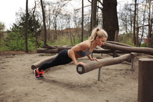 Tough young woman doing pushups on a log at park. Fit young woman exercising in woods. ** Note: Soft Focus at 100%, best at smaller sizes