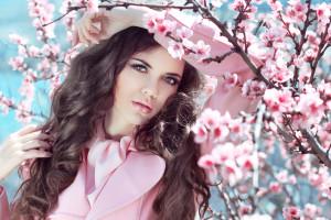 Beautiful brunette girl posing over Pink Spring Cherry blossoms. Enjoyment. Beauty girl.