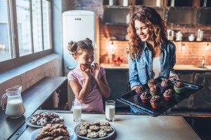 Attractive young woman and her little cute daughter are eating cakes and cookies on kitchen and drinking milk. Having fun together while enjoying freshly baked pastries.