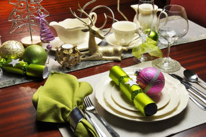 Modern and stylish Christmas dinner table setting including plates glasses and placemats bon bons and Christmas decorations. Landscape horizontal orientation.
