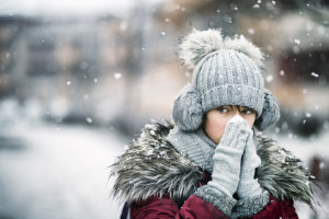 Portrait of teenage girl blowing hos nose on a snowy winter day. Nikon D850