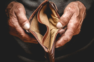 Empty wallet in the hands of an elderly man. Poverty in retirement concept