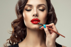 Makeup artist applies  red lipstick on lips . Beautiful woman face. Make up detail. Beauty girl with perfect skin and make-up. Red lips and nails manicure