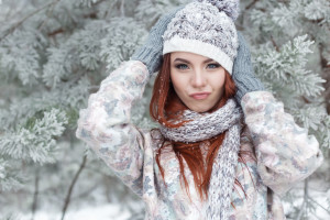 beautiful cheerful cute red-haired girl in a cap and scarf plays with snow in the beautiful forest fairy