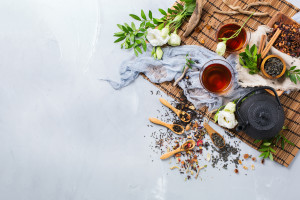 Food and drink still life concept. Selection assortment of different japanese chinese herbal masala tea infusion beverage teapot with white flowers on the table. Top view copy space background