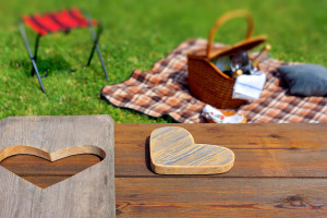 Picnic table with wooden heart blanket and basket in the grass. Background with space for text or image. ** Note: Shallow depth of field