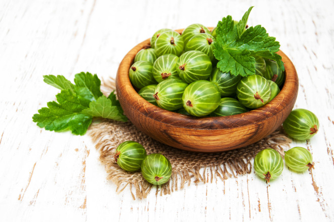 gooseberries with leaves on a old wooden background