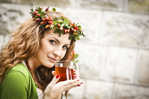 Beautiful young woman holding a cup of rosehip tea