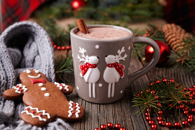 Cup of hot chocolate or cocoa with cinnamon and gingerbread man cookie in new year tree decorations frame on vintage wooden table background. Homemade traditional celebration recipe. Rustic style.