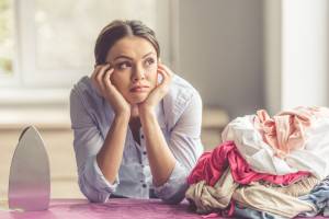 Beautiful bored young woman is leaning on ironing board and looking away while ironing clothes at home