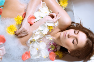 Spa body care for sensual relaxation: picture of beautiful sexy young woman pinup girl having fun relaxing in bath with flowers petals on milk copy space water background.