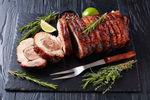 overhead view of sliced roast pork roulade -  Porchetta, delicious pork roast of Italian culinary holiday tradition on a slate tray with rosemary and lime, close-up