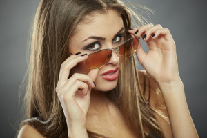 Flirtatious woman holding and looking over sunglasses with seductive eyes on grey background.