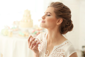Beautiful young woman with bottle of perfume at home